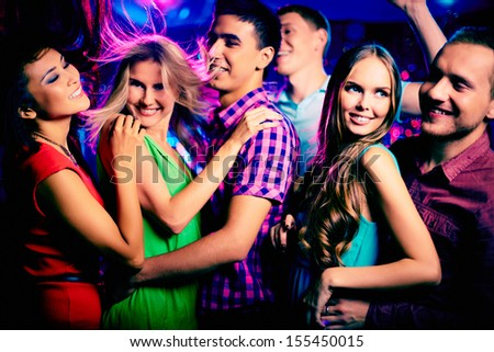 Happy young friends dancing at disco
