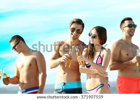 Happy young friends drinking beer at the beach, on sky background