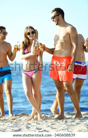 Happy young friends drinking beer at the beach, outdoors - stock photo