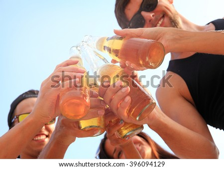 Happy young friends drinking beer outdoors - stock photo