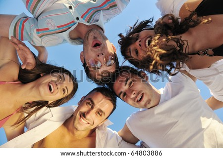 happy young friends group team huging have fun and celebrate  on the beach at the sunset