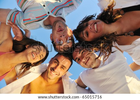 happy young friends group team huging have fun and celebrate  on the beach at the sunset - stock photo