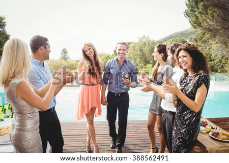Happy young friends having drinks at swimming pool and enjoying holiday - stock photo