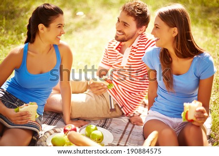 Happy young friends having picnic in the country