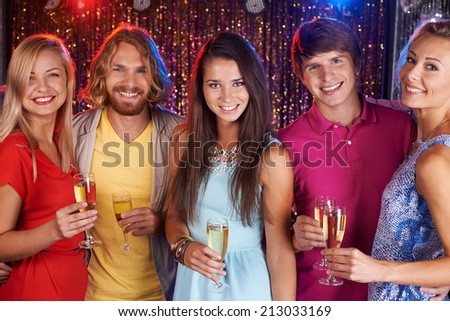 Happy young friends holding flutes with champagne - stock photo