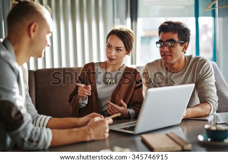 Happy young friends or employees talking at meeting - stock photo