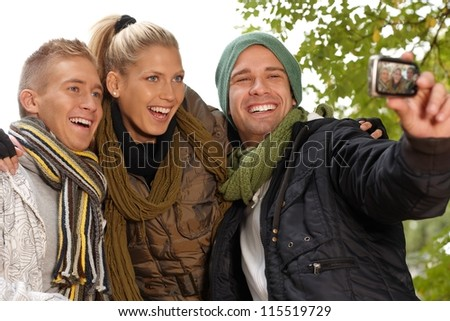 Happy young friends photographing themselves in park at autumn. - stock photo