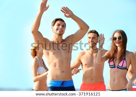 Happy young friends relaxing at the beach, outdoors - stock photo