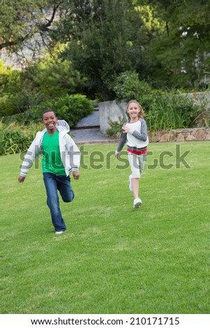 Happy young friends running towards the camera in the park - stock photo
