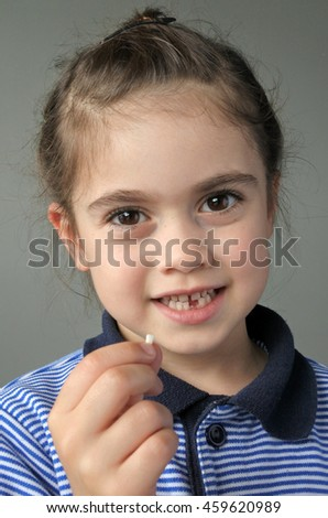 Happy young girl (age 6) holds her first falling milk teeth, looks at the camera. Childhood healthcare concept. real people copy space - stock photo