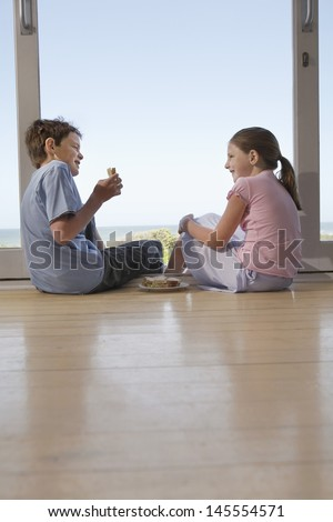 Happy young girl and boy eating sandwiches in doorway - stock photo