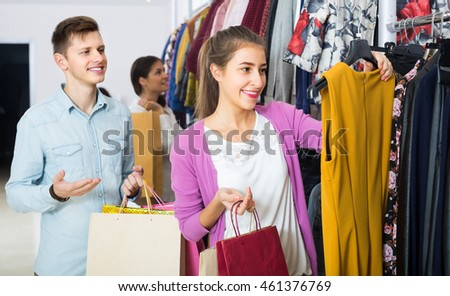 Happy young girl and her boyfriend doing many purchases at the clothing shop
