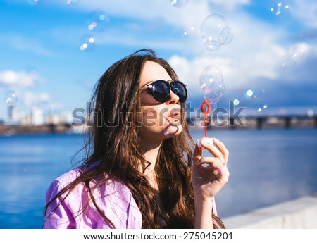 Happy young girl blowing soap bubbles outdoor - stock photo