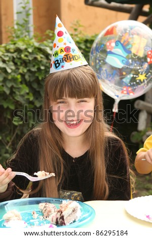 Happy Young Girl Celebrating Her Birthday by Eating Cake