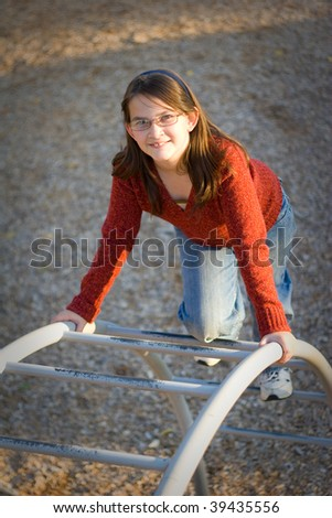 Happy young girl climbing on playground - stock photo
