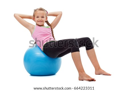 Happy young girl doing abdominal gymnastic exercises sitting on large rubber ball and smiling - isolated