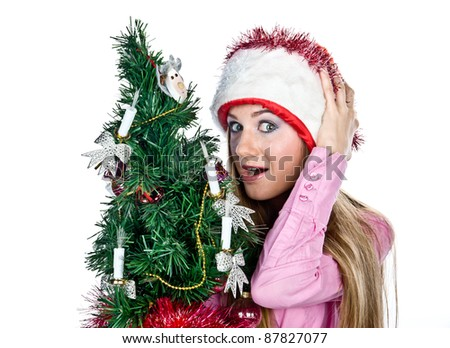 happy young girl dressed as Santa with a Christmas tree in his hand, isolated over white