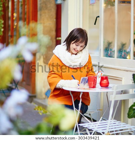 Happy young girl drinking coffee in a Parisian street cafe and writing Christmas greetings in postcards on a winter day - stock photo