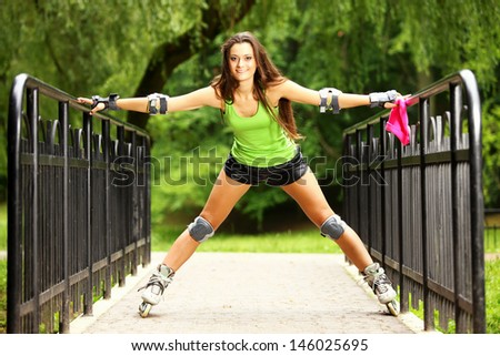Happy young girl enjoying roller skating rollerblading on inline skates sport in park. Woman in outdoor activities
