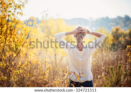 Happy young girl enjoying the beauty of sunny autumn day  in high grass in an autumn park. View from a back. - stock photo