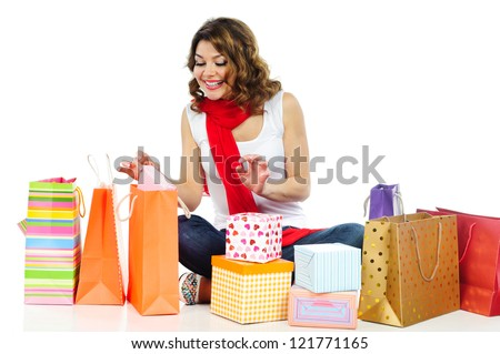 Happy young girl exploring presents in shopping bags