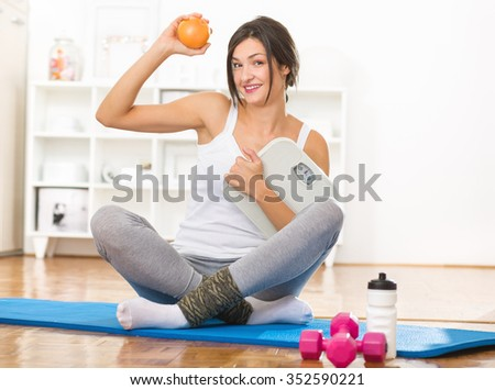 Happy young girl holding an orange and a weight scale in her hands after work out