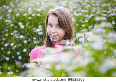 happy young girl in a meadow with camomiles - stock photo