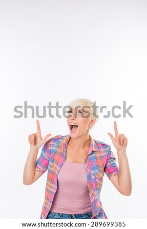 Happy young girl in casual shirt pointing up