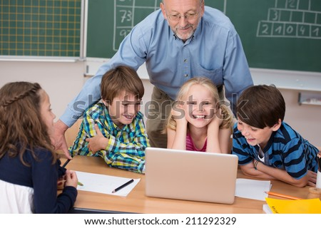 Happy young girl in class with her two class mates sitting at a desk while a male teacher leans over them from behind - stock photo