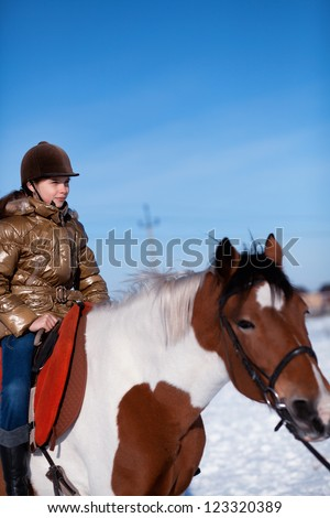 Happy young girl in coat and hat riding horse - stock photo