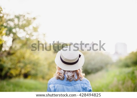 Happy young girl in hat enjoying the beauty of spring day in the park - stock photo