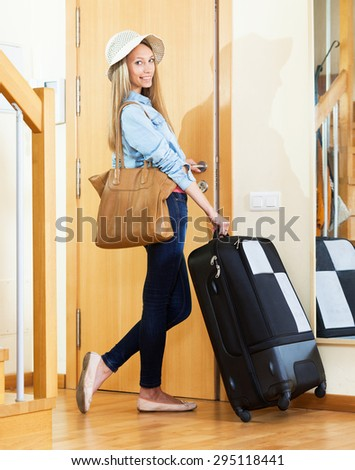 Happy young girl in hat going on vacation with  suitcase - stock photo