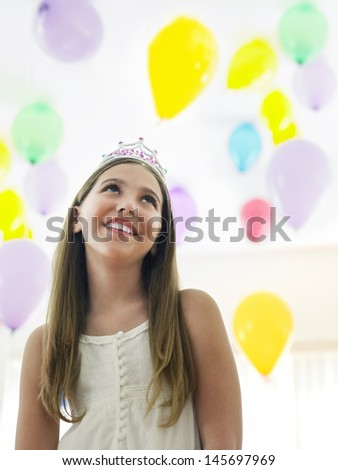 Happy young girl in tiara looking up against colorful balloons - stock photo