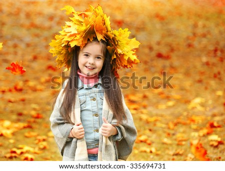 Happy young girl in yellow autumn wreath  in park - stock photo