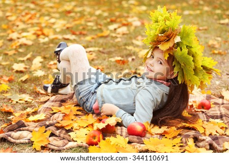 Happy young girl in yellow autumn wreath lying on plaid in park