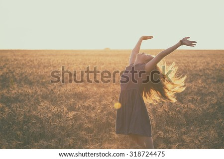 happy young girl joys at the wheat field at the evening time