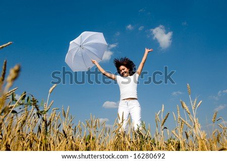Happy young girl jumping for joy with umbrella in the field - stock photo