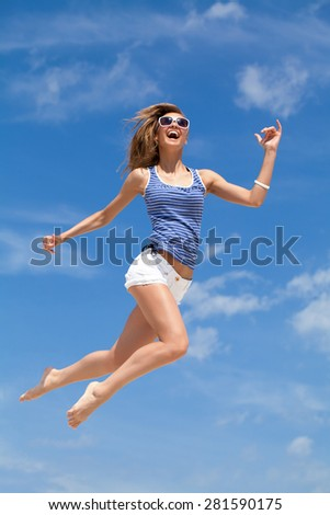 Happy young girl jumping in blue sky