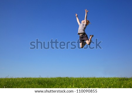 Happy young girl jumping in the meadow - stock photo