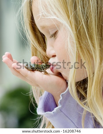 Happy young girl kissing a frog - stock photo