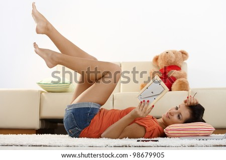 Happy young girl laying on floor at home, looking at boyfriend photo, smiling. - stock photo