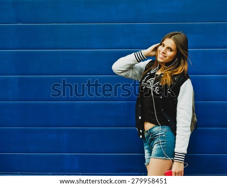 Happy young girl listening music  in headphones over blue wall background - stock photo