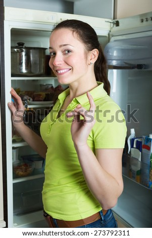 Happy young girl looking for something in fridge at kitchen