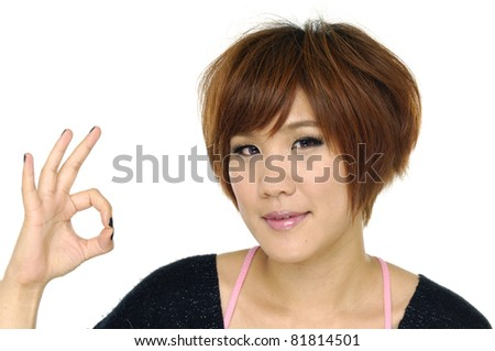 Happy young girl making ok hand sign - stock photo