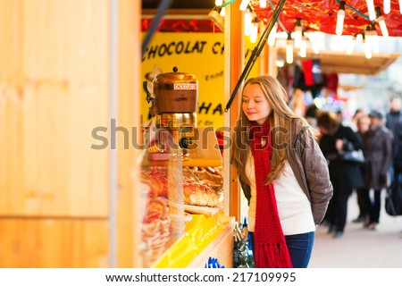 Happy young girl on a Parisian Christmas market, selecting Christmas treats