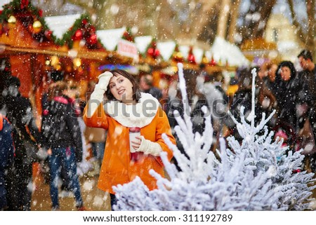 Happy young girl on a Parisian Christmas market, selecting Christmas treats and drinking hot beverage during snowfall - stock photo