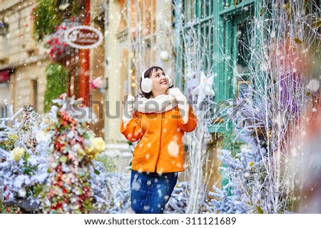 Happy young girl on a Parisian street cafe on winter day during snowfall - stock photo