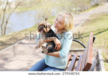 Happy young girl owner with yorkshire terrier dog walking in the park