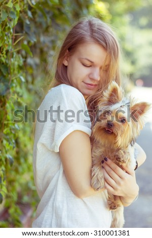 Happy young girl owner with yorkshire terrier dog walking in the park - stock photo