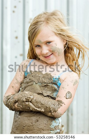 happy young girl playing in the mud - stock photo